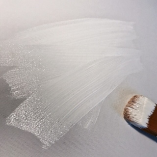 Paintbrush loaded with white gesso laying on a white canvas alongside strokes of white paint.