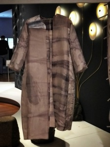 Photo from the exhibit of an open-front silk coat dyed using Chieza's process. It is a brown grey with both horizontal and vertical seepage shaped streaks of a dull purple. The coat has no buttons, collar or cuffs.