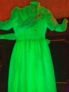 Photograph of the front of one of the three Fantasma dresses. It glows green with the aide of glasses, is long sleeved with a plane collar and button up front.  Fantasma by Another Farm Photo: J Hartnett-Henderson © 2019