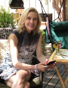 Jennifer seated in dappled shade wearing the dress